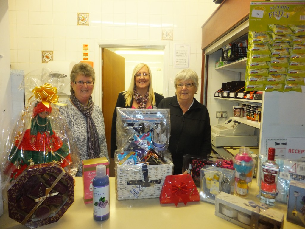 Volunteer Co-ordinator Julia Griffiths with Volunteers Anne Davies and Margaret Evans with some of the gifts and raffle prizes available at the Christmas Fete