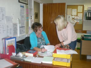 Volunteer Receptionist Maria Hynes discussing a message with Community Clinical Nurse Specialist Jane Coles